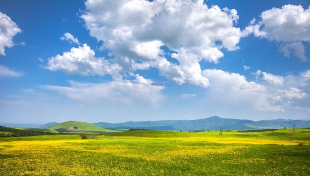 Зеленые луговые холмы и голубое небо с облаками, исследуя армению