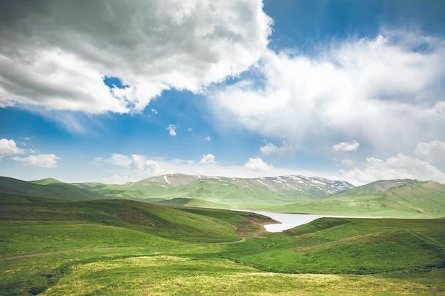 Озеро зеленый луг и голубое небо с облаками, исследуя армению