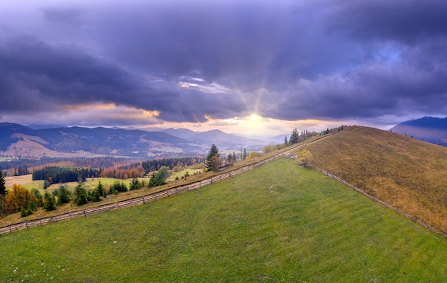 Зеленый луг или пастбище в осенних горах на рассвете.