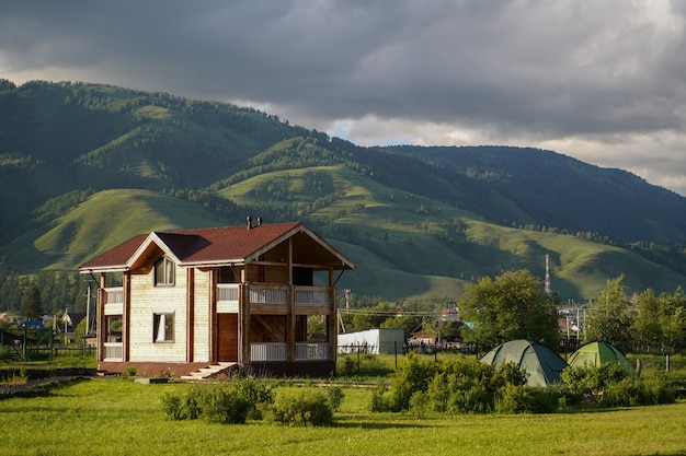 Green meadow with touristic cottage and touristic tents, and growed mountains