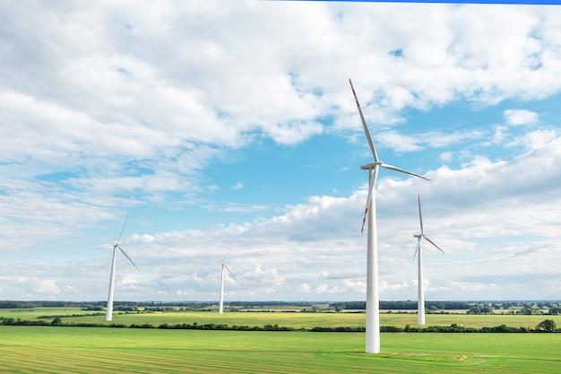 発電する風力タービンのある緑の牧草地、青い空のある夏の風景、代替エネルギー源