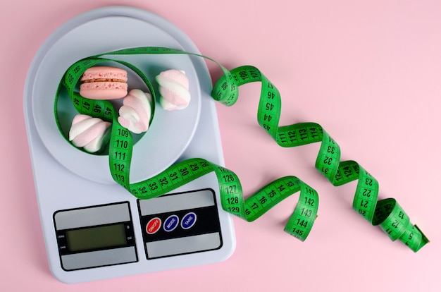 Green measuring tape, digital kitchen scales with macarons and marshmallows on pastel pink.
