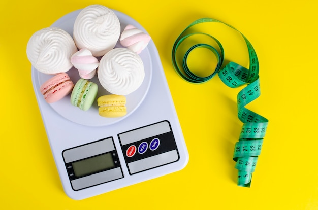 Green measuring tape, digital kitchen scales with macarons and meringues on yellow