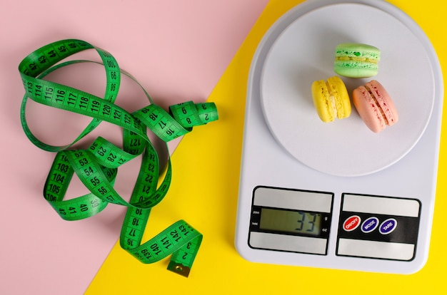 Green measuring tape, digital kitchen scales with macarons on yellow and pink. no diet day