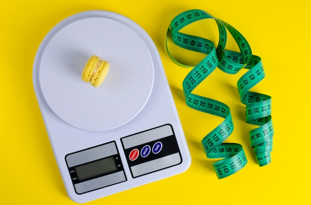 Green measuring tape, digital kitchen scales with macarons on yellow