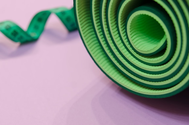 A green measuring tape twisted into a spiral and a mat for fitness lie on a purple background