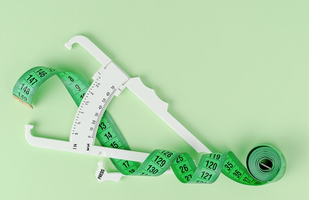 Green measuring tape and white caliper.