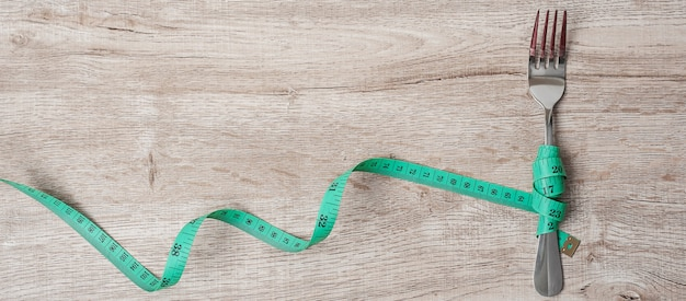 Green measuring tape wrapped around fork and knife on wooden table background