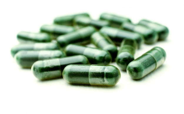 Green medical pills on white background, selective focus