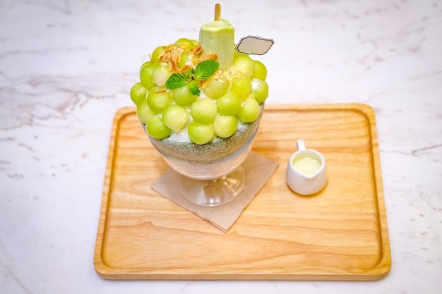Green melon ball shape are arranged on the top of bingsu (korean ice-cream style) and decorated with green tea ice-cream and mint leaf on the wood plate and sweetened condensed milk beside.