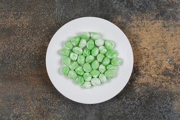 白いプレート上の緑のメントールキャンディー。