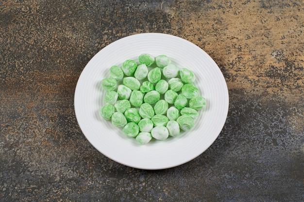 Caramelle al mentolo verdi sulla zolla bianca.