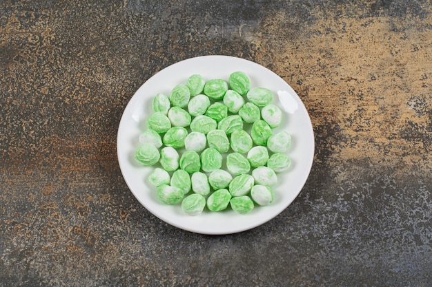 Green menthol candies on white plate.