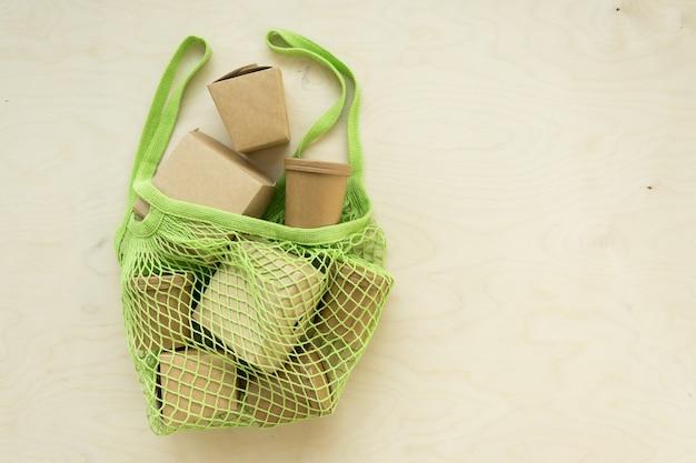 Зеленая сетчатая сумка-тоут с упаковочными коробками