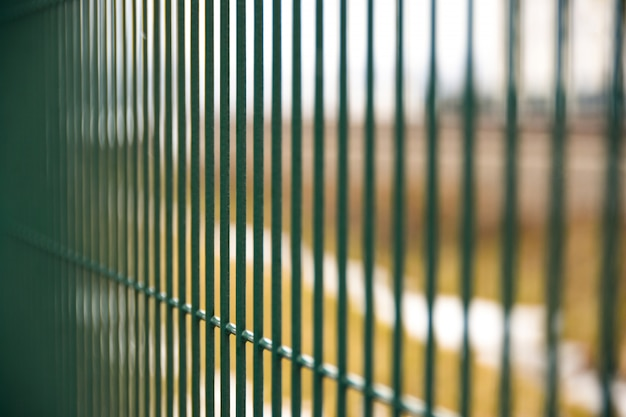 Green metal fence from rods on the street