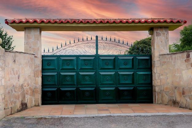 Зеленые металлические ворота с кованым узором и часть каменного забора