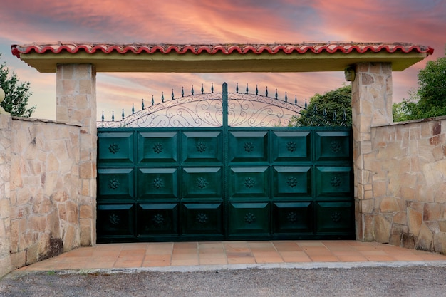 Green metal gates with a forged pattern and part of a stone fence