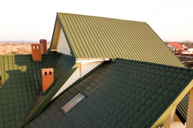 Зеленая металлическая черепичная крыша дома с чердачным пластиковым окном и кирпичным камином.