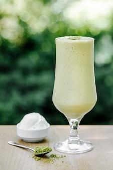 Зеленый молочный коктейль с мороженым на террасе.