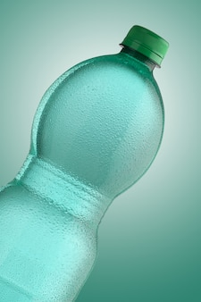 Green mineral water bottle with drops, on green