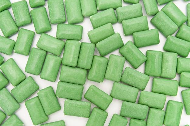 녹색 민트 껌 정제가 무작위로 흩어져 있습니다. 흰색 배경에 고립