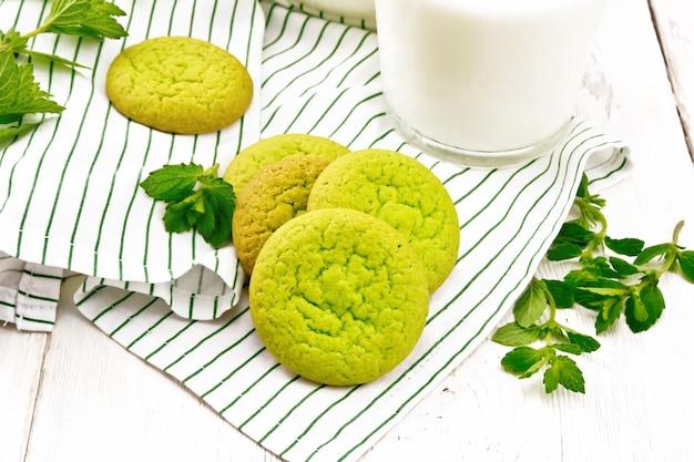 木の板の背景にガラスのミルクとタオルの上の緑のミントクッキー