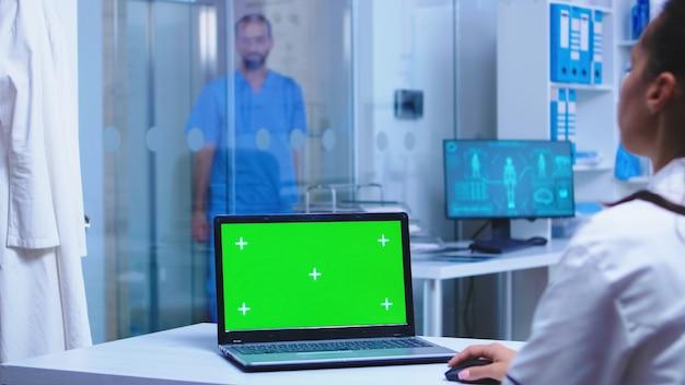 Modello verde sul computer portatile del medico in ospedale e infermiere che aprono la porta di vetro dell'armadio.