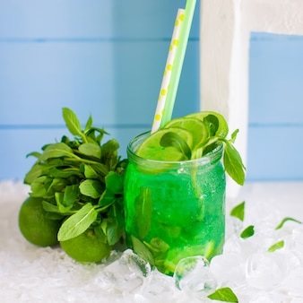 Green mojito served in glass jar garnished with lime and mint