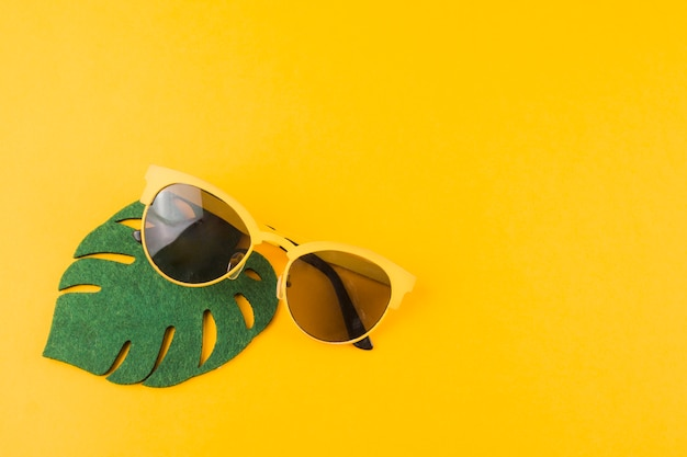 Green monstera leaf with sunglasses on yellow background