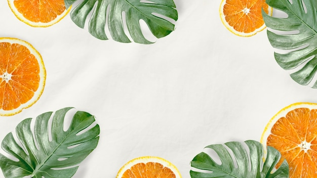 Зеленые листья монстеры и апельсин