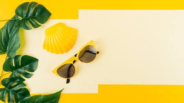 Green monstera leaves with sunglasses and scallop on paper against yellow background