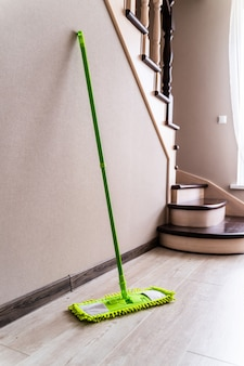 Green mop on a wall and stairs background. cleaning living room.