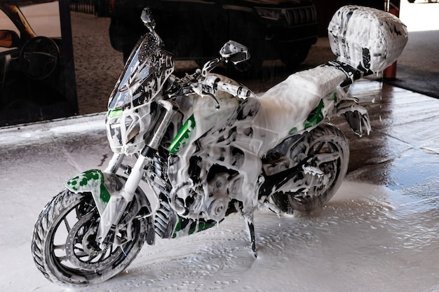 Green motorcycle in foam at the car wash