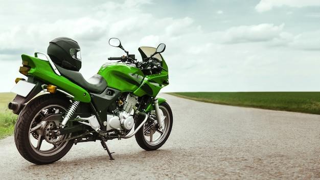 녹색 오토바이는 시골길에 서 있다
