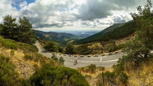 道路とサイクリストが下る緑の山の風景。