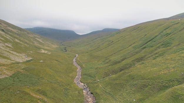 녹색 산 경로 공중. 언덕에서 흐린 봉우리까지 좁은 길.