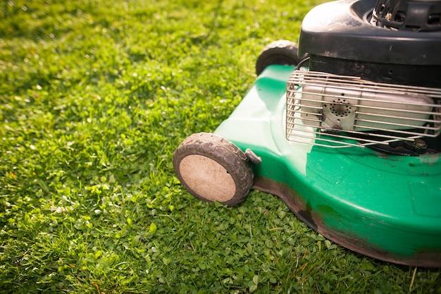 Зеленая косилка на свежей весенней траве