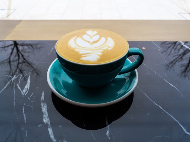 A green mug of cappuccino sits on a black marble table.