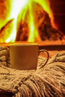 Green mug for tea or coffee, wool things near cozy fireplace