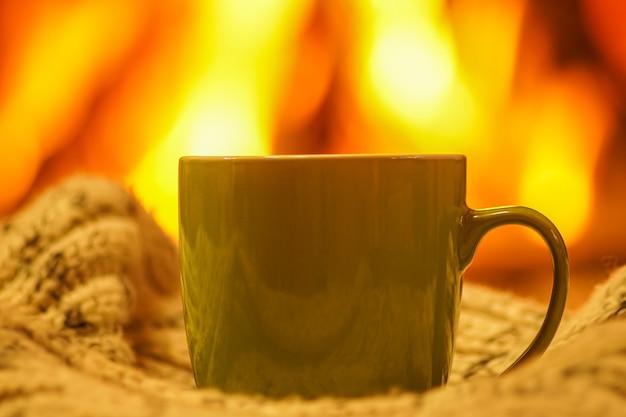 Green mug for tea or coffee and wool things near cozy fireplace
