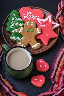 Green mug with hot chocolate and multi-colored gingerbread cookies in a bowl