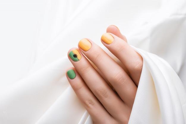 緑の爪のデザイン。色のマニキュアで女性の手。