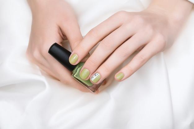 녹색 네일 디자인. 반짝이 매니큐어와 여성의 손입니다.