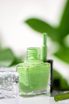 Зеленая бутылка лака для ногтей на белой поверхности.