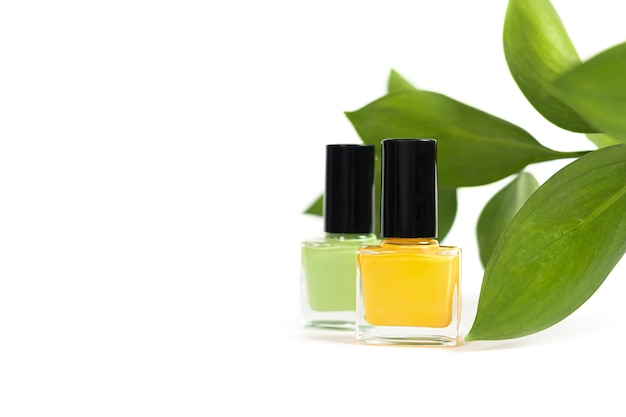 Green nail polish bottle on white surface.
