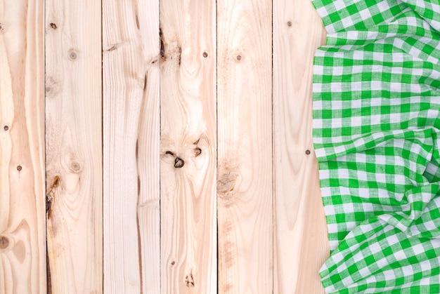 木製のテーブル、上面に緑のナプキン布