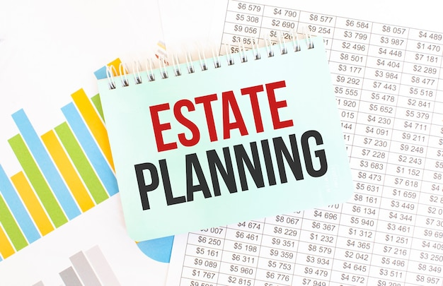 Green notepad on financial documentation. text estate planning.