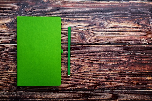 Green notepad with a felt-tip pen on a brown wooden table, top view.