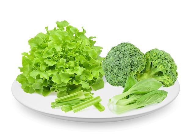 흰색 배경에 분리된 접시에 녹색 참나무 상추, 청경채, 셀러리, 브로콜리