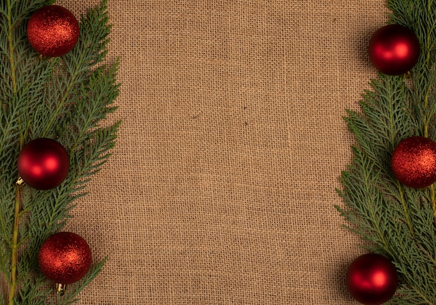 Green oak tree branches with red christmas balls on the two sides.